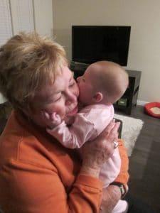 Baby Hannah chewing on Grandma's cheeks